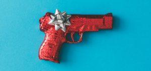 Une arme est emballé dans du papier cadeau à paillette rouge sur fond bleu