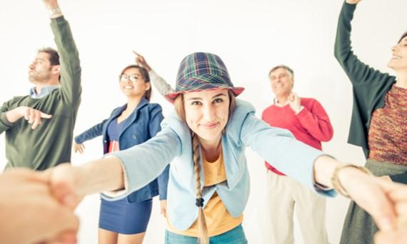 Jeune femme souriante avec un chapeau entourée de personnes heureuses
