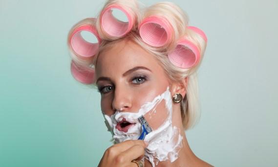 Belle femme blonde avec des bigoudis rose en train de se raser