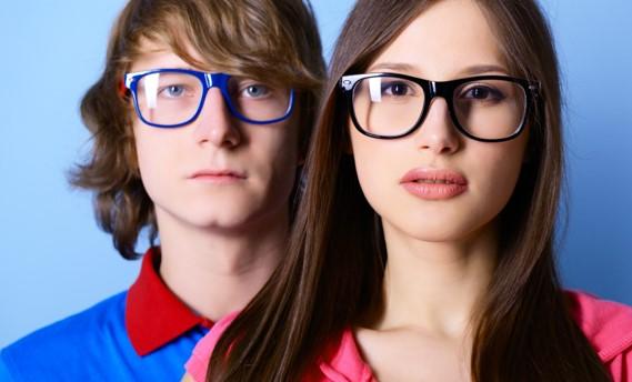 Homme et femme jeune avec des lunettes, sérieux et côte à côte