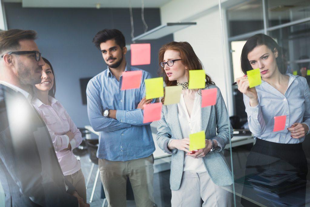 Un groupe de professionnels travaillent avec des post-it sur un tableau