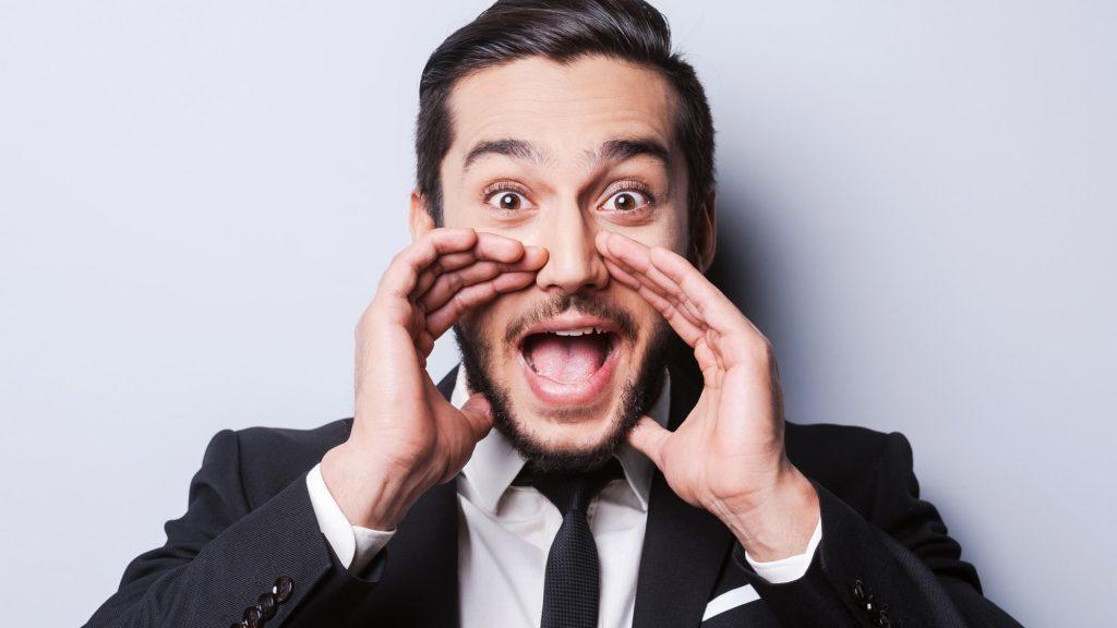 Homme brun en costume noir qui crie quelque chose en mettant ses mains autours de sa bouche