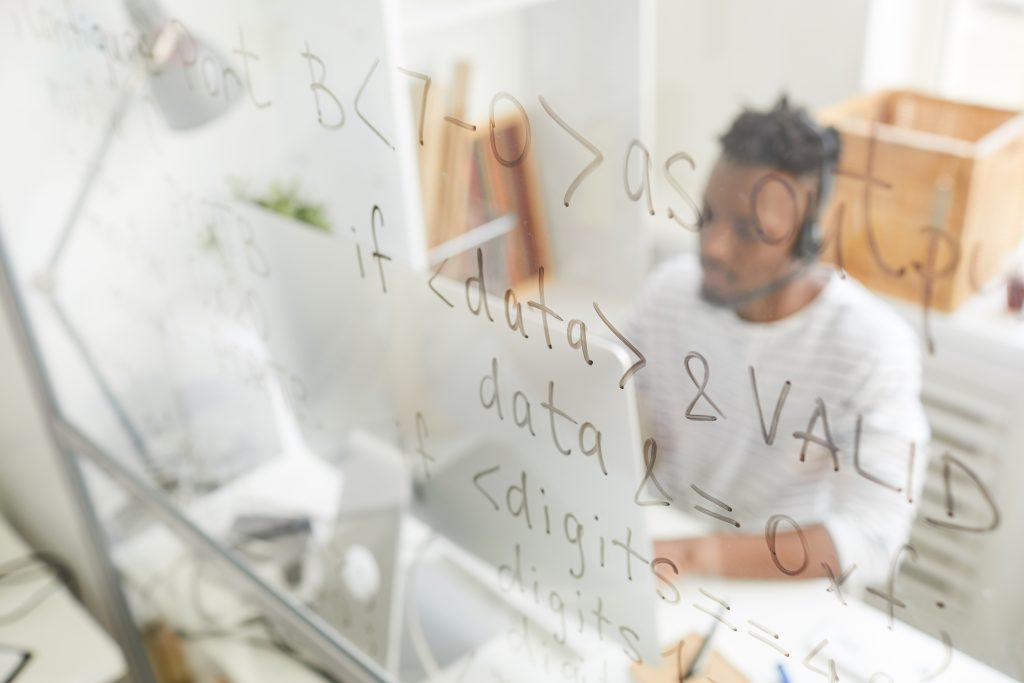 Un homme travaille sur son ordinateur. Il y a un filtre sur l'image sur lequel est écrit un code.