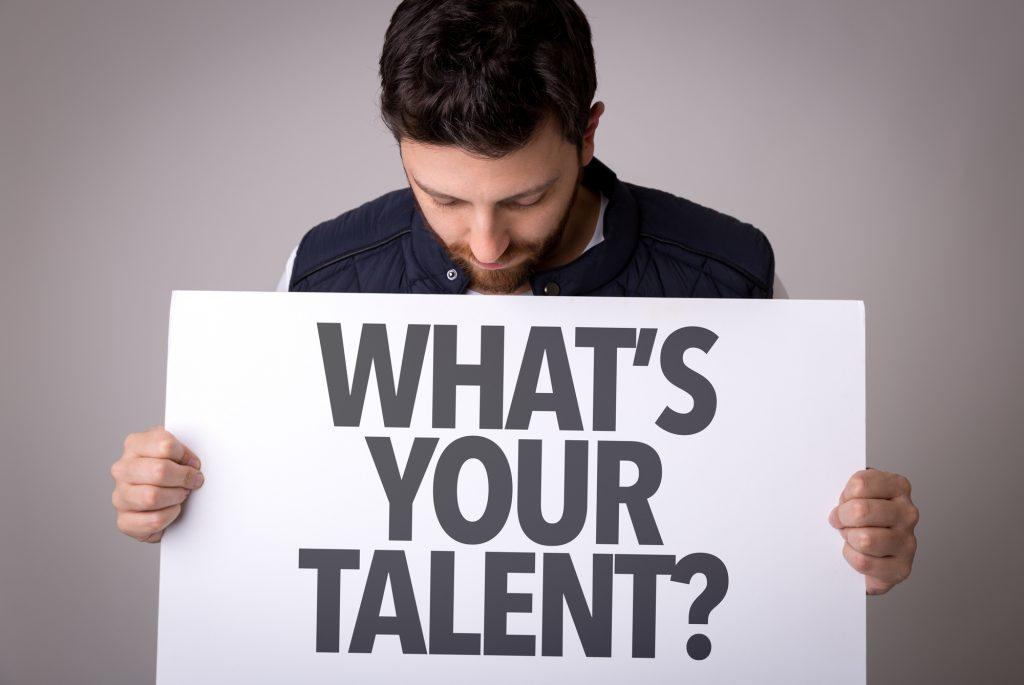 """Un homme tient une pancarte avec marquée """"Wath's your talent"""""""