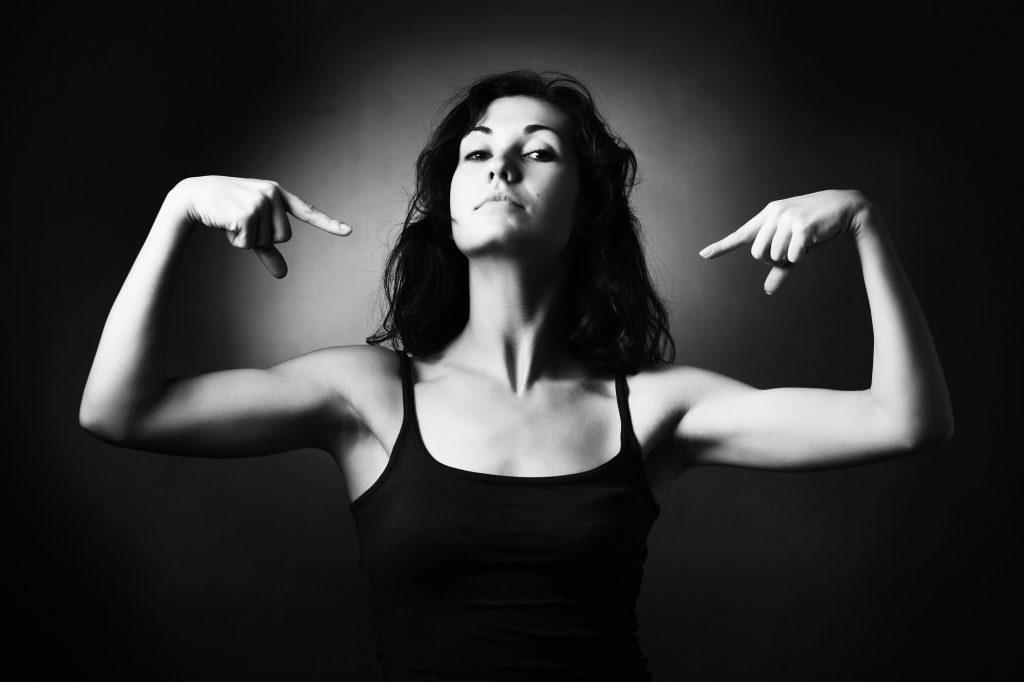 Femme en débardeur en noir et blanc se montre du doigt