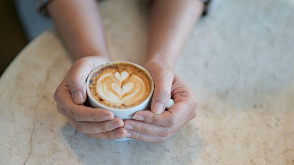 Latte café texture coeur à la main.