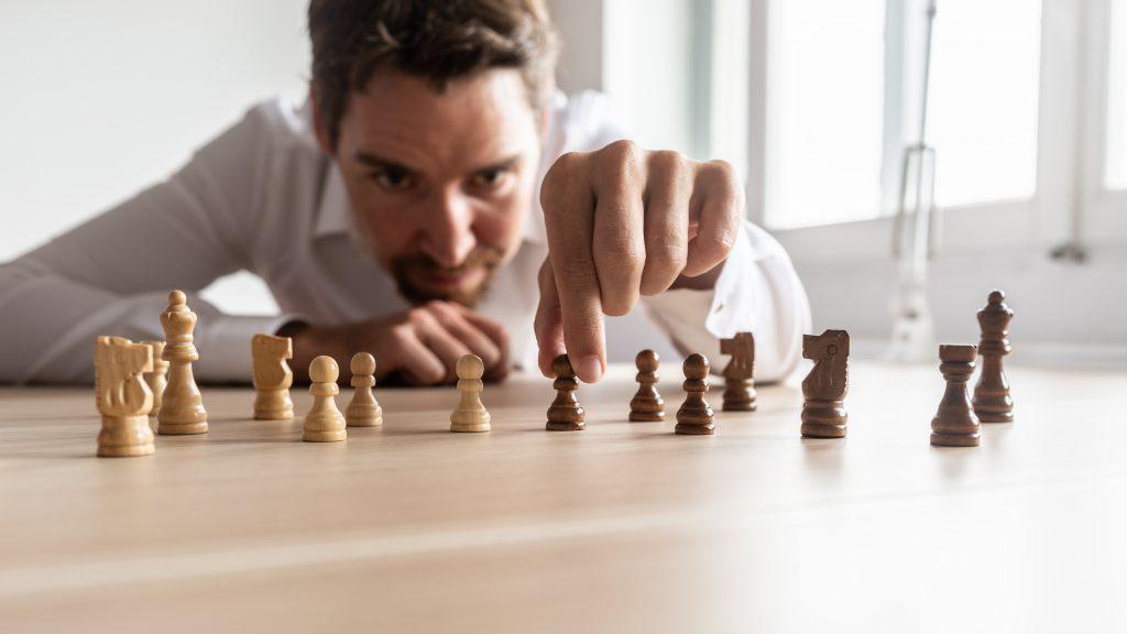 Un homme d'affaires place une pièce sur un jeu d'échec